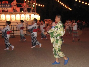 A man doing a Bonodori dance while holding a baby