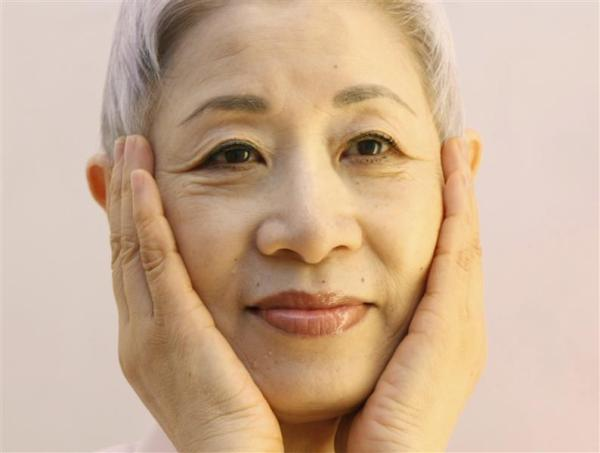 Japanese beauty expert Chizu Saeki cups her cheeks, which is part of her facial care, at her salon in Tokyo