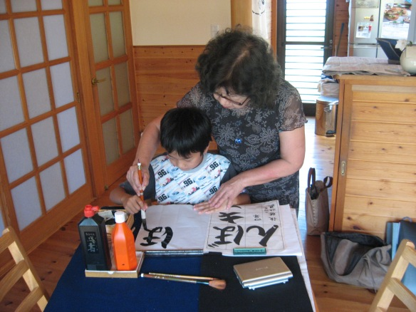 japanese calligraphy teacher teaching her grandson