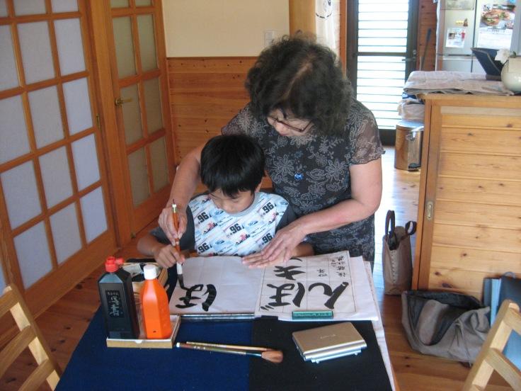japanese calligraphy teacher teaching her grandson