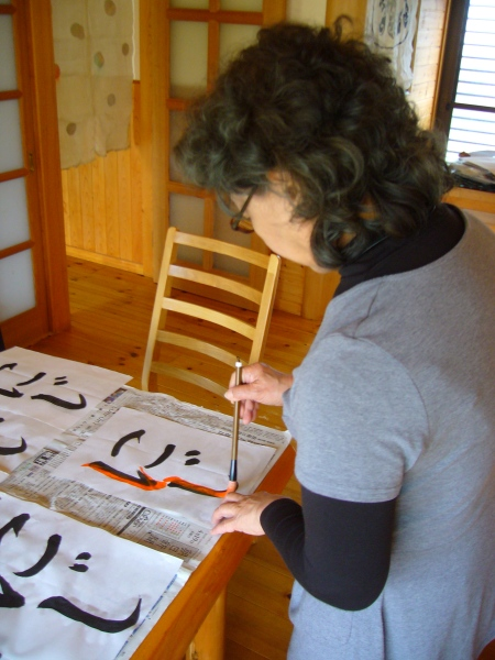 a japanese calligraphy teacer makes corrections in orange ink